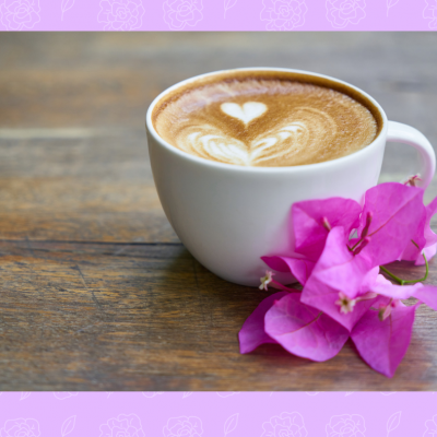 A cup of coffee with a purple flower