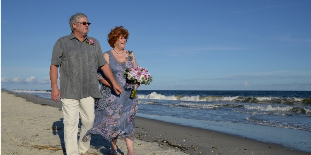 Randy and Louise walking on the beach on their wedding day