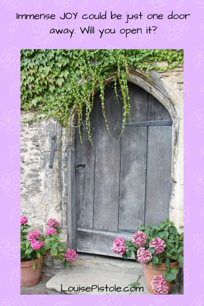 A wooden doorway with ivy and potted geraniums