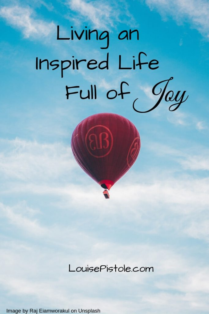 A red hot air balloon sailing through clouds in a blue sky. Living an inspired life full of JOY.
