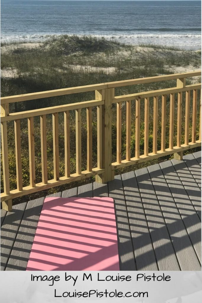A pink yoga mat on a deck overlooking the ocean.